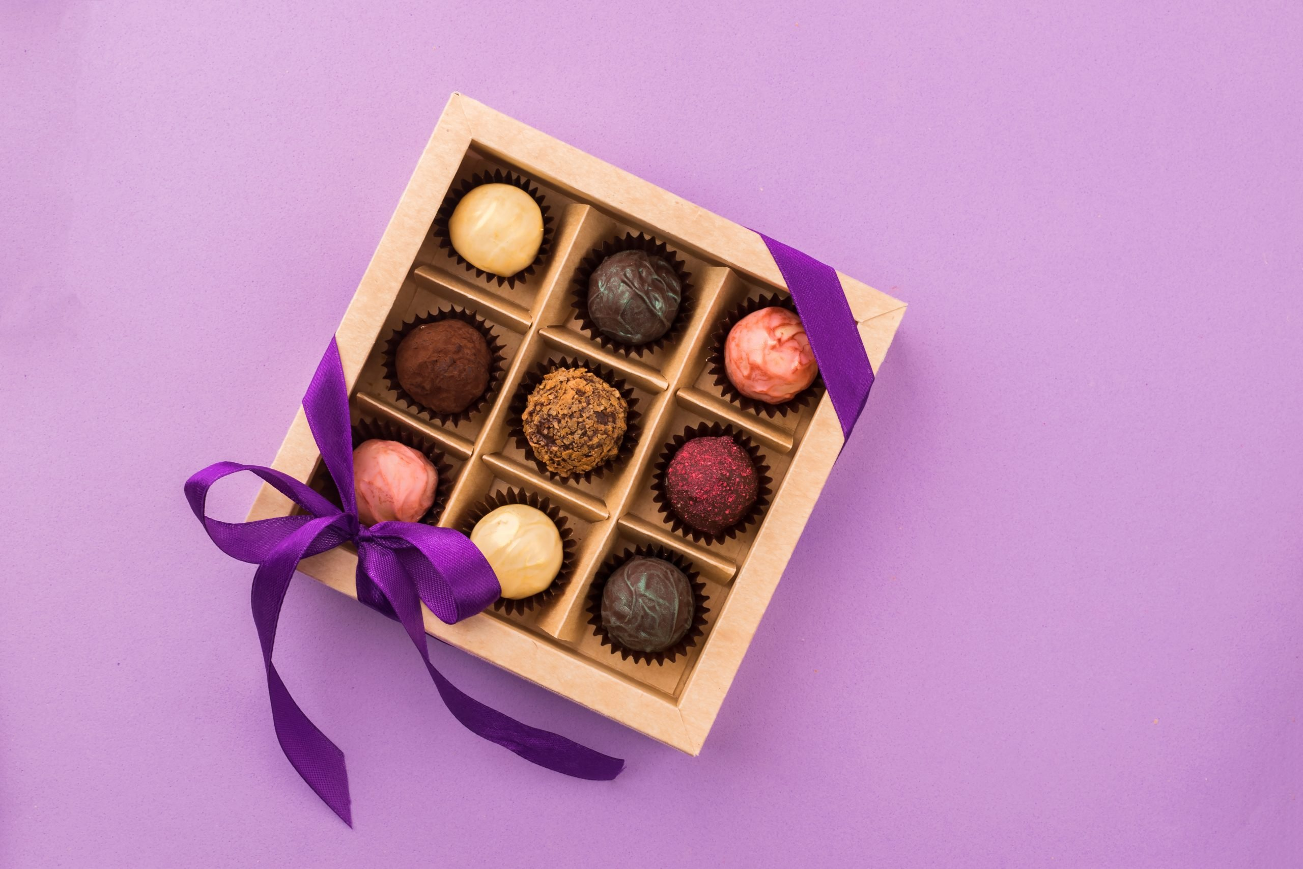 A set of assorted chocolates in a paper box with a satin purple ribbon on a bright background. A place for design. Flat layout. Celebratory concept. Copy space